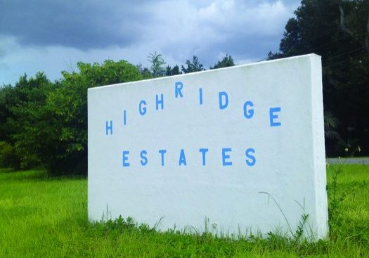 Picture of Sign at Entrance to High Ridge on State Road 100. Sign Reads: High Ridge Estates. Sign is white with blue letters.